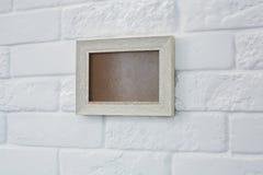Lege omlijsting bij witte bakstenen muur Stock Foto