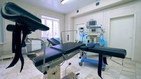 Lege onderzoeksstoel in een gynaecologische het ziekenhuisruimte stock footage