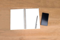 Lege open notaboek en mobilofoon op houten achtergrond Mening Stock Foto's
