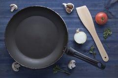 Lege pan met paddestoelen, tomaat, knoflook, ui, peterseliebladeren en houten spatel op blauwe houten lijst Stock Foto's