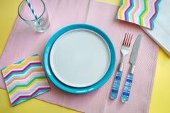 Lege plaat en blauw Bestek op roze achtergrond concept het voorbereidingen treffen te eten stock foto's