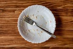 Lege plaat van voedsel na maaltijd op een houten lijst Stock Afbeelding