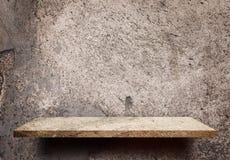 Lege plank op grungy muur van het vuilcement voor productvertoning Stock Afbeelding
