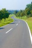 Lege plattelandsweg bij de zomer Stock Fotografie