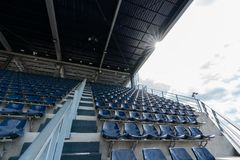 Lege Rijen van de zetels van de stadiontribune of stadionzetels met zonnestraal op dak en wolkenhemel, plastic blauwe en witte ze stock fotografie