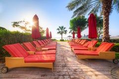 Lege rode deckchairs bij het overzees Stock Fotografie