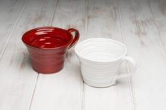 Lege Rode en Witte Met de hand gemaakte Koppen op Wit Houten Comité Stock Afbeelding