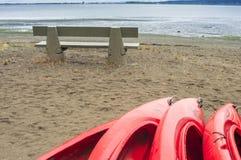 Lege rode plastic recreatieve die kajaks voor huur of huur, op zandig strand na uren op een regenachtige dag wordt opgeslagen Cre Royalty-vrije Stock Afbeeldingen