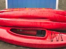 Lege rode plastic recreatieve die kajaks voor huur of huur, op zandig strand na uren op een regenachtige dag wordt opgeslagen Cre Royalty-vrije Stock Foto's