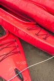 Lege rode plastic recreatieve die kajaks voor huur of huur, op zandig strand na uren op een regenachtige dag wordt opgeslagen Cre Stock Afbeelding