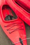 Lege rode plastic recreatieve die kajaks voor huur of huur, op zandig strand na uren op een regenachtige dag wordt opgeslagen Cre Royalty-vrije Stock Afbeelding