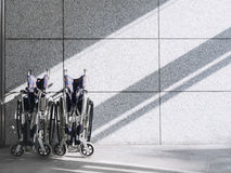 Lege Rolstoel op muurachtergrond met schaduwverlichting Royalty-vrije Stock Foto's
