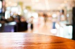 Lege rondetafelbovenkant bij koffiewinkel vage achtergrond met bok Stock Afbeelding