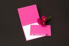 Lege roze kaart met harten en chrysantenbloemen op zwarte B Stock Afbeelding