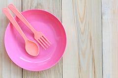 Lege roze plastic die schotel en lepel op houten vloer wordt geplaatst Royalty-vrije Stock Fotografie