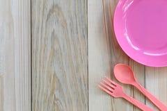 Lege roze plastic die schotel en lepel op houten vloer wordt geplaatst Royalty-vrije Stock Afbeeldingen