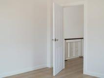 Lege ruimte met open deur en witte binnenlandse muurachtergrond royalty-vrije stock afbeeldingen
