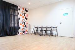 Lege ruimte met stoelen en gordijnen op venster Stock Afbeelding