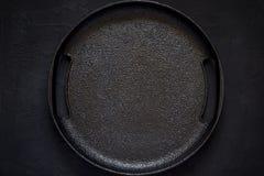 Lege rustieke gietijzerplaat op een zwarte achtergrond Hoogste meningsverstand Royalty-vrije Stock Afbeeldingen