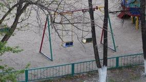 Lege schommelingszetel die op verlaten speelplaats slingeren stock video