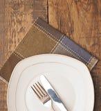 Lege schotel, mes en vork en bruin servet Royalty-vrije Stock Afbeelding