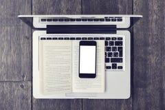 Lege smartphone op open boek en laptop op een vloer Stock Fotografie