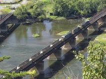 Lege steenkoolauto's die spoorwegbrug kruisen stock afbeelding