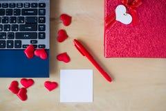 Lege sticker, PC, pen, vakje verfraaide harten op houten lijst Stock Fotografie