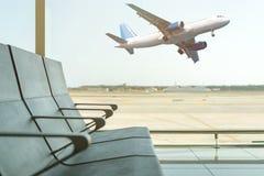 Lege stoelen in de vertrekzaal bij luchthaven op achtergrond van vliegtuig het opstijgen reis concept royalty-vrije stock afbeeldingen