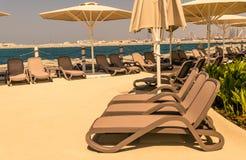 Lege strandbanken en paraplu's stock afbeeldingen