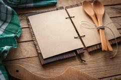 Lege uitstekende receptenkookboek en werktuigen op houten achtergrond, exemplaarruimte stock afbeelding