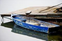 Lege verlaten blauwe boot in een dok stock afbeelding