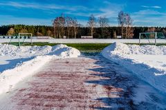 Lege Voetbal ( Soccer) Gebied in de Winter gedeeltelijk in Sneeuw wordt behandeld - Sunny Winter Day dat royalty-vrije stock foto's