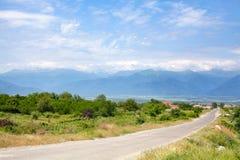 Lege weg in het platteland, bergen op de horizon en de blauwe hemel met wolkenachtergrond stock fotografie