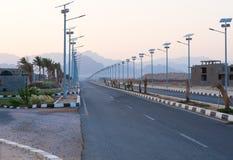Lege weg tussen rij van zonnepanelen op de lantaarns en pa Stock Foto