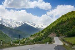 Lege wegkronkelweg in de bergen, blauwe hemel met wolken, bergpieken op de sneeuw en de groene heuvelsachtergrond stock afbeeldingen