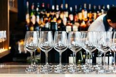 Lege wijnglazen op tegenlijst met onduidelijk beeldwijn, alcoholische drank en geesten op achtergrond stock fotografie