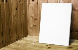 Lege witte affiche die bij houten muur in plank houten ruimte leunen, Moc royalty-vrije stock afbeeldingen