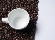 Lege witte ceramische koffiekop op koffiebonen Stock Afbeelding