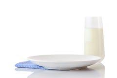 Lege witte ceramische plaat op blauw servet in klein wit stippen en glas melk Stock Foto's