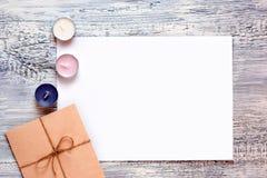 Lege witte groetkaart en envelop met kaarsen over rustieke lijst met exemplaarruimte Spot omhoog Royalty-vrije Stock Foto's