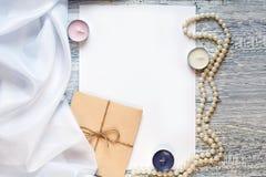 Lege witte groetkaart en envelop met kaarsen, parels over rustieke lijst met exemplaarruimte Spot omhoog Stock Afbeelding