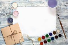 Lege witte groetkaart en envelop met kaarsen, parels en waterverfverven over rustieke lijst met exemplaarruimte Spot omhoog Royalty-vrije Stock Foto's