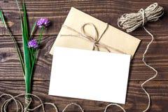 Lege witte groetkaart en envelop met purpere wildflowers Royalty-vrije Stock Afbeeldingen