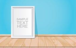 Lege witte omlijsting op de blauwe muur en de houten vloer Royalty-vrije Stock Afbeelding