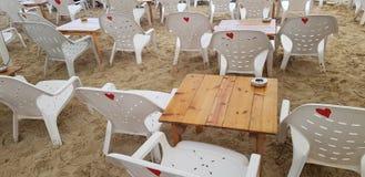 Lege witte plastic stoelen en houten lijsten royalty-vrije stock afbeeldingen