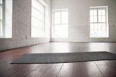 Lege witte ruimte, zolderstudio, yogamat op de vloer Stock Afbeeldingen