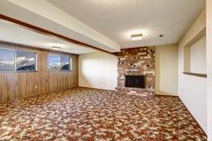 Lege woonkamer met baksteenopen haard en kleurrijke tapijtvloer Stock Afbeeldingen