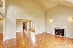 Lege woonkamer met hoge plafond en open haard Stock Afbeelding
