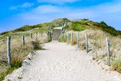 Lege zandige weg met treden door duinen die tot het strand leiden stock foto's